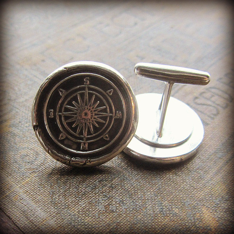 Two Compass Cuff Links displayed on a table