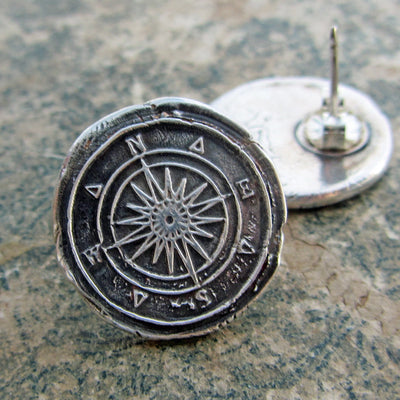 Compass wax seal earrings on marble counter