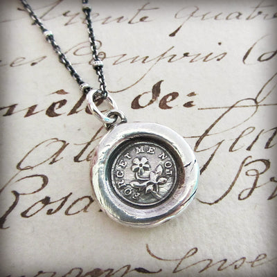 Forget Me Not flower wax seal necklace over old english font