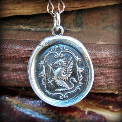 A silver griffin wax seal crest laying over a stack of old style book covers.