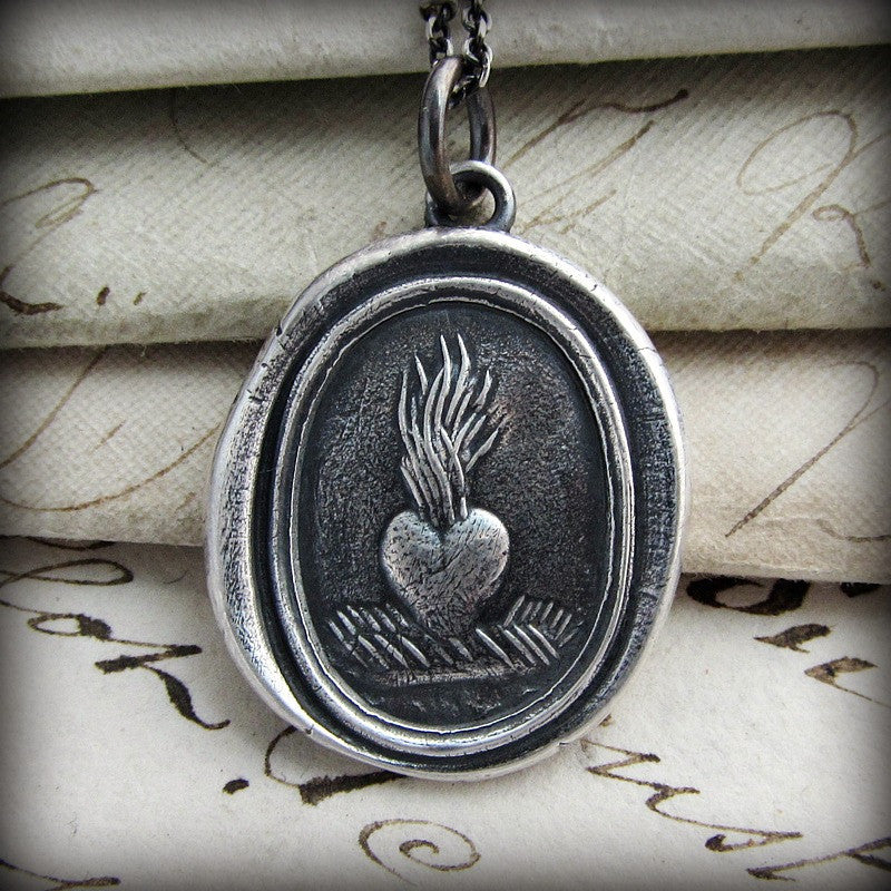 Ardent love heart wax seal necklace over old english script.