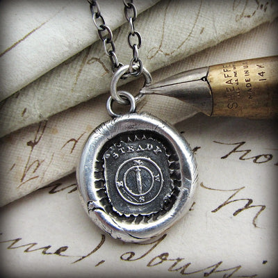 Mariners compass wax seal next to a fine tipped pen and old english font