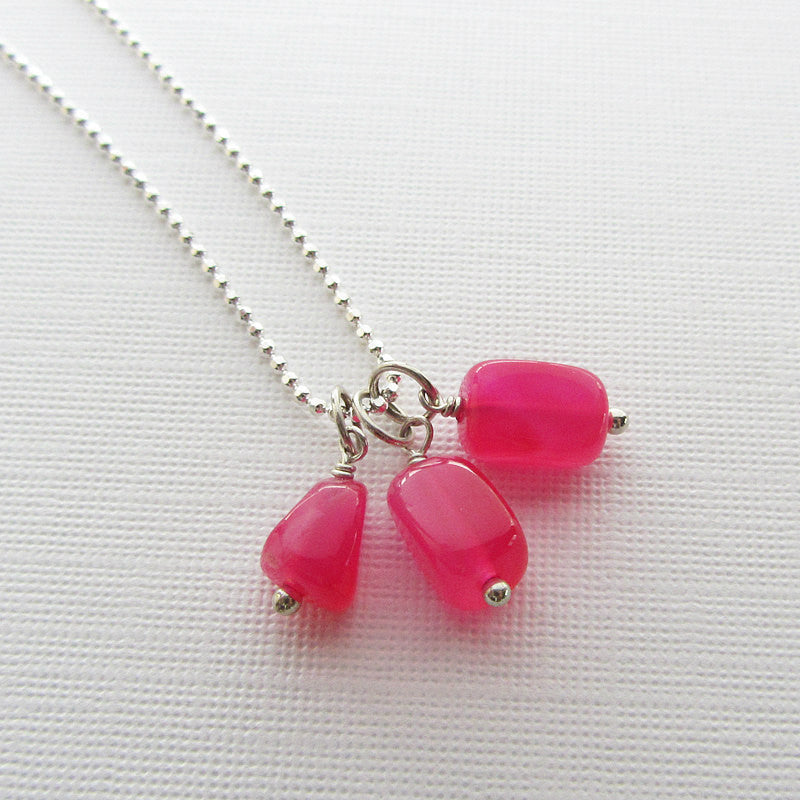 Three hot pink chalcedony nugget charms attached to a stainless steel chain.