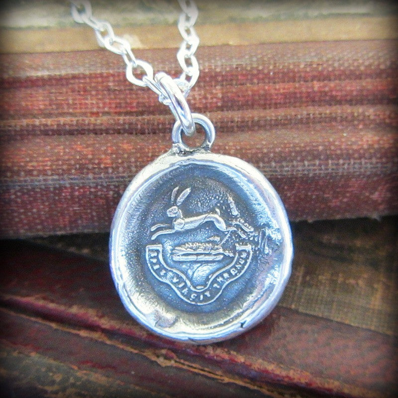 Rabbit wax seal crest necklace with the phrase hope conquers all.