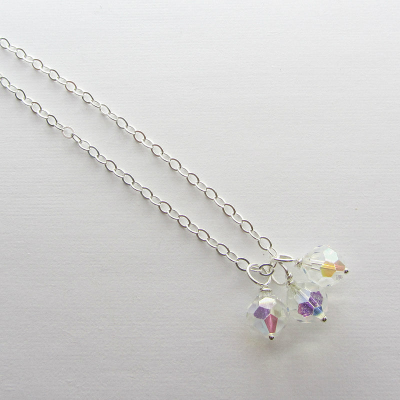 Three vintage reclaimed swarovski crystal attached to a chain with a white background