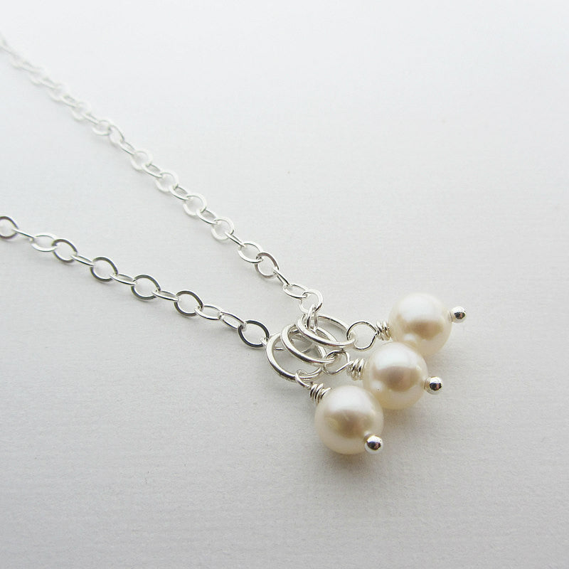 Three fresh water pearls attached to a chain to make a necklace.