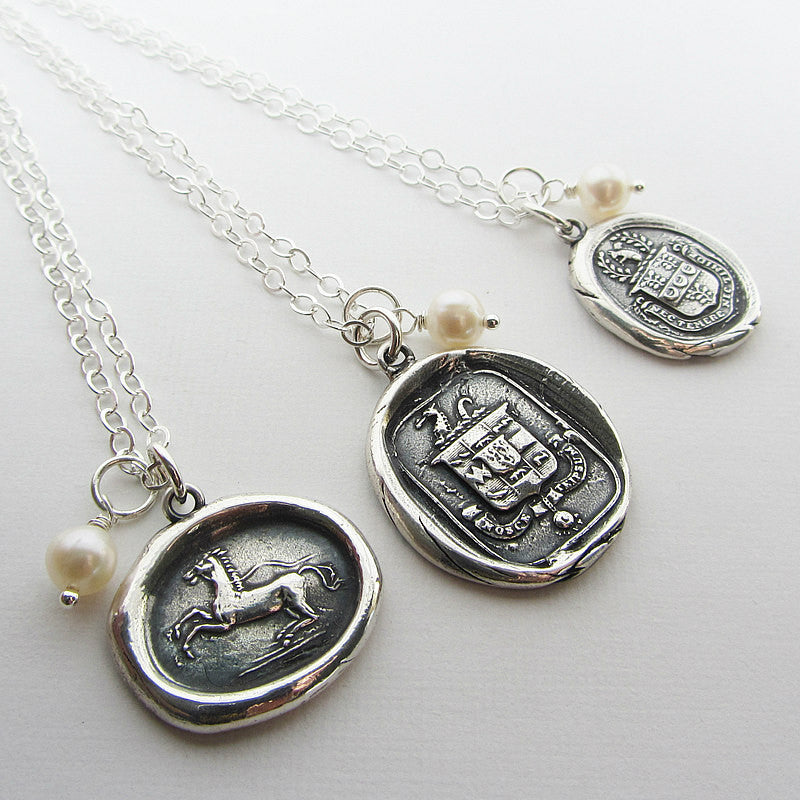Wax seal necklaces with freshwater pearls attached.