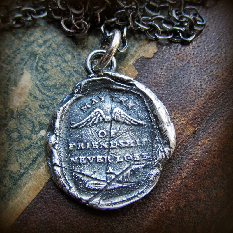 Winged wax seal pendant with the motto May the Wings of Friendship Never Lose a Feather