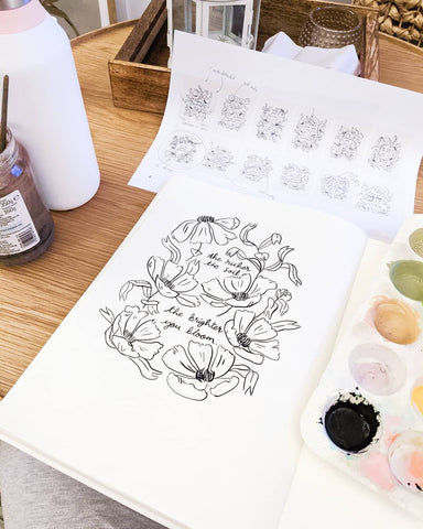 """an illustration in a sketchbook reads """"the richer the soil the brighter you bloom"""" in black calligraphy, surrounded by black line art flowers"""