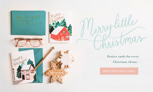 "Christmas cards - one with a snowy cabin in the woods, and another of a pink, snow-topped cottage. They're surrounded by christmas cookies, a pen, reading glasses and lettering that reads ""Merry little Christmas - festive cards for every christmas theme"