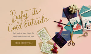 "A cascade of pretty Christmas Greetings cards surrounded by ribbons, pencils, scissors and tape. Some lettering reads ""Baby it's Cold Outside"" and underneath says ""It's on it's way, shop the Christmas collection now"""
