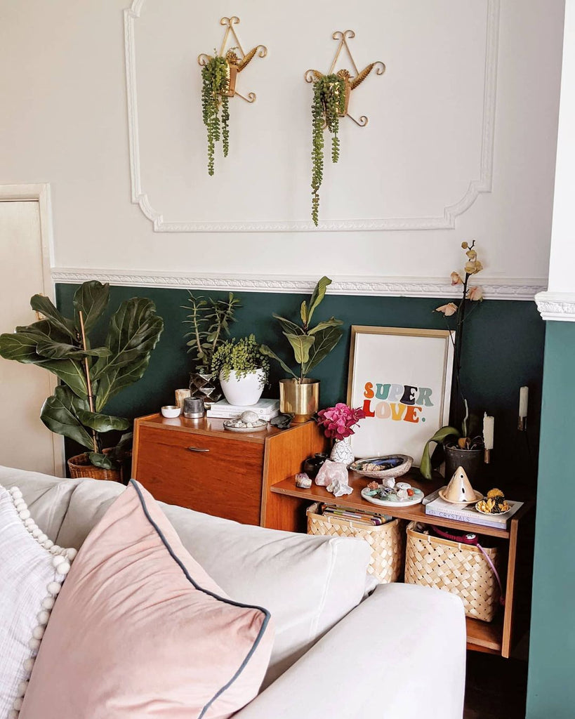 bright, sunny living room painted half-height in a deep green colour and filled with plants, vintage furniture and a rainbow print nestled on the side cabinet