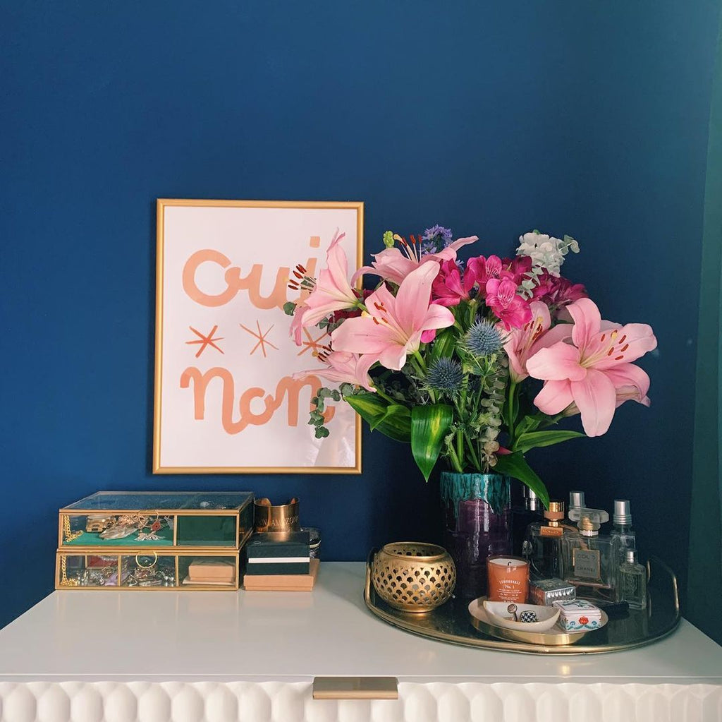 A bedroom painted deep blue, with a white textured dresser. On top stands a bunch of pink lilies, jewellery storage, and above it a pink lettered french print hangs on the wall