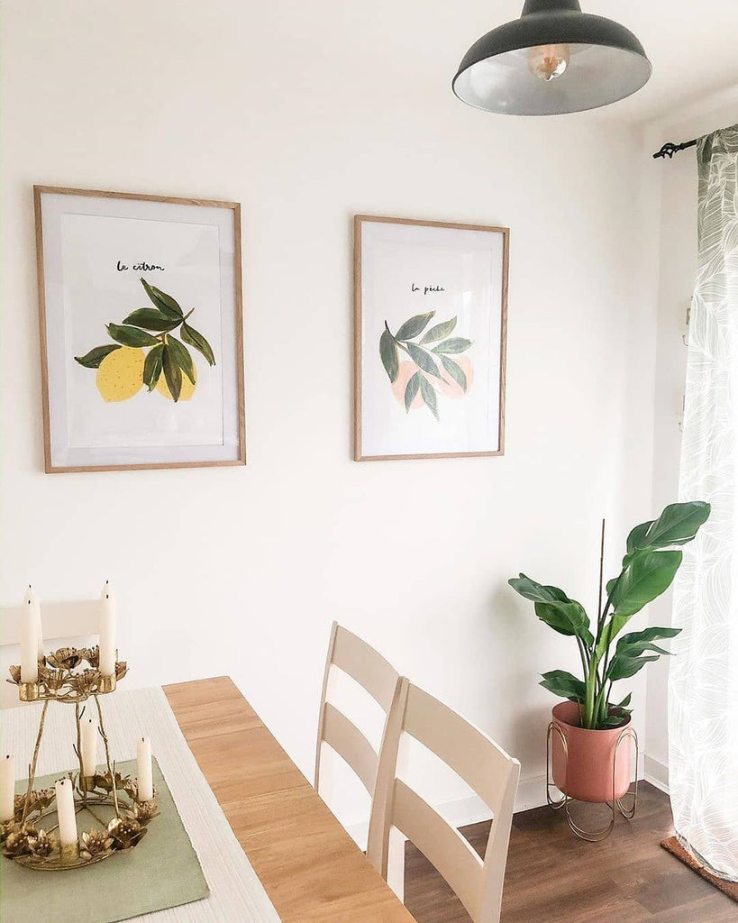 A bright, light kitchen with a dining table, with peach and lemon art prints in wooden frames hanging above