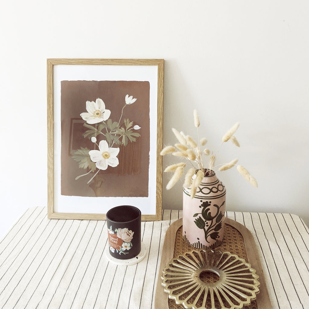 a brown and white japanese anemone print in a natural wood frame, propped up on a striped cotton tablecloth with a candle, vase and table decorations