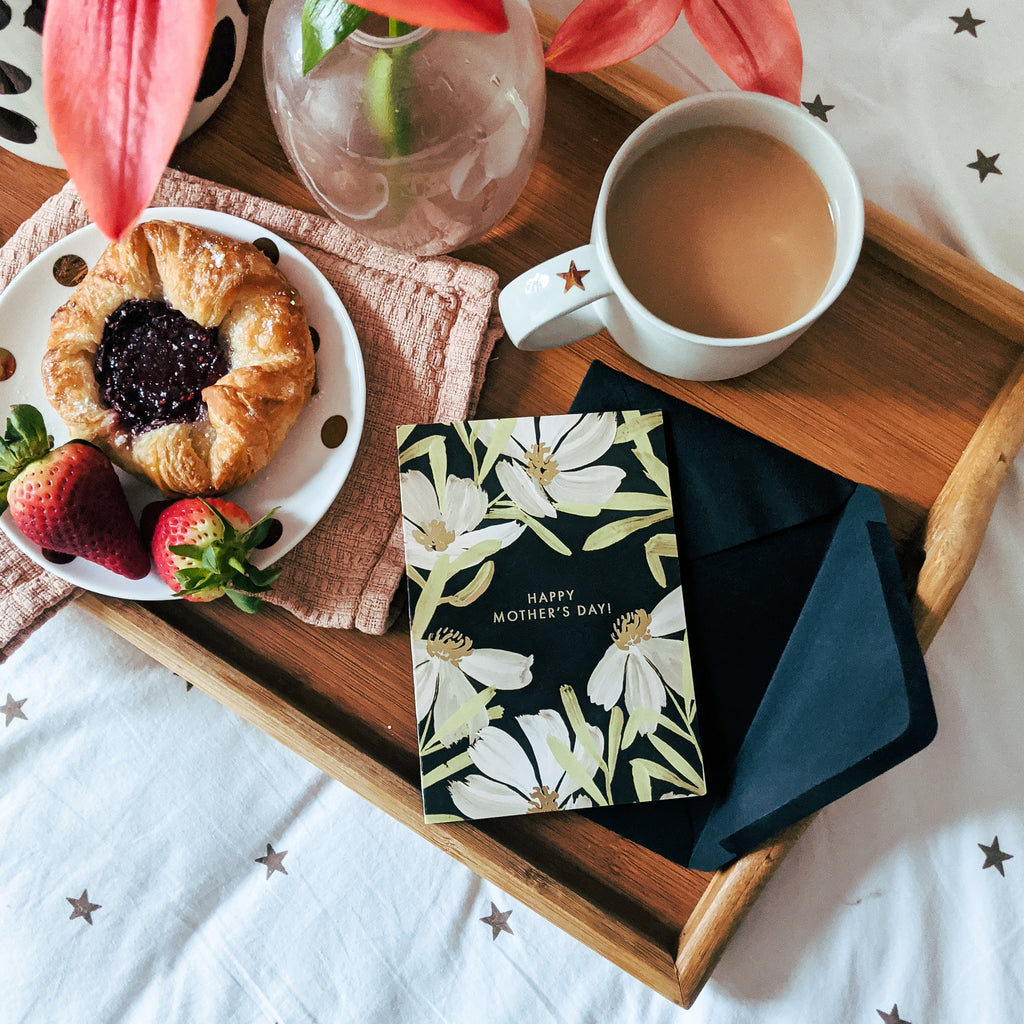 a floral mother's day card sitting on a breakfast in bed tray of coffee, pastries and flowers