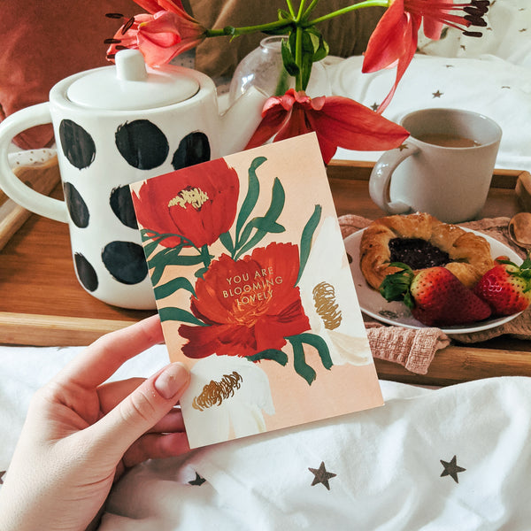 """holding a floral card that says """"you are blooming lovely"""" in gold foil, infront of a breakfast in bed tray of tea and pastries"""