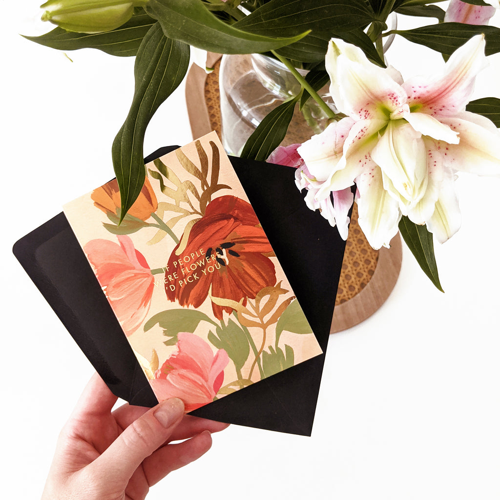 """holding a floral patterned card with gold foil lettering that reads """"if people were flowers, I'd pick you"""". A bouquet of lilies can be seen in the top right corner."""