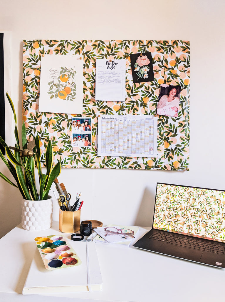 A light and airy home office space with a noticeboard decorated with peach wrapping paper