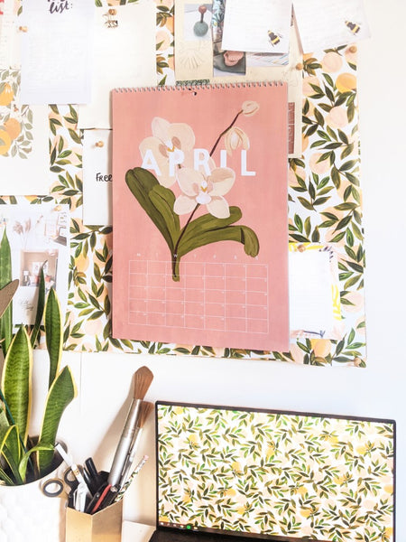 """A floral illustrated calendar turned to """"april"""", hanging on a noticeboard above a desk"""