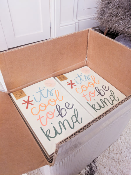 "A shipping box full of wrapped up ""cool to be kind"" notebooks"
