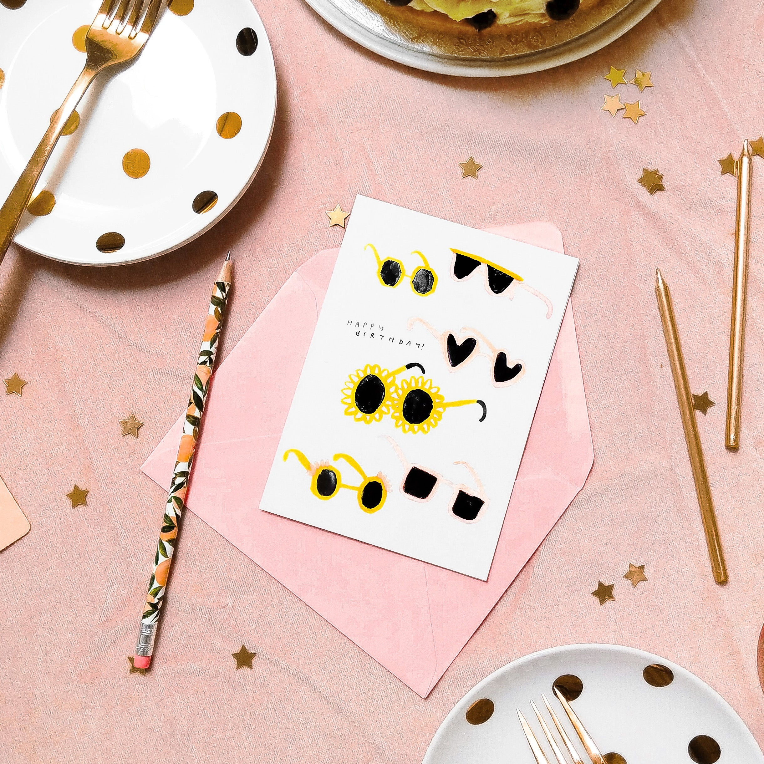 a white card with illustrated sunglasses on, on a pink party tablecloth