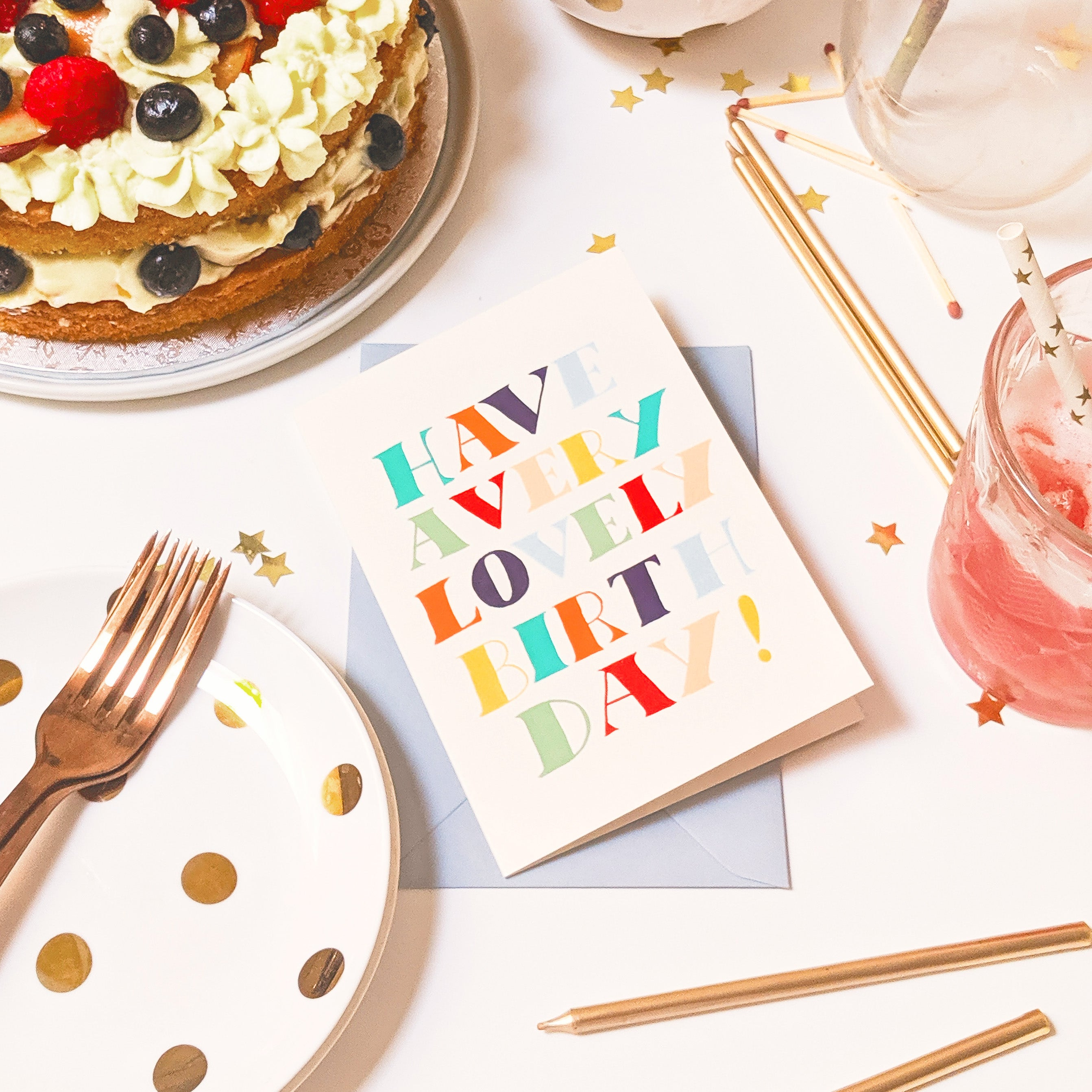 a typographic birthday card surrounded by cake, candles and drinks