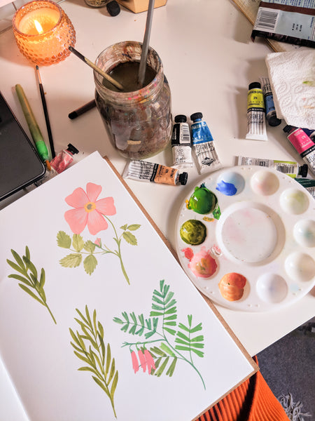 painting florals in my sketchbook with paints and brushes around me