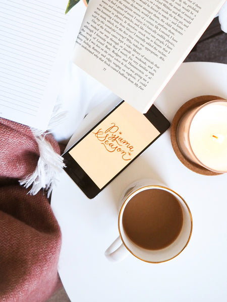 a white coffee table holding a smartphone, cup of coffee, book and a candle