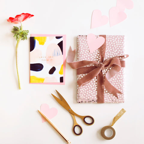 A beautifully wrapped gift, flowers and stationery for valentines day