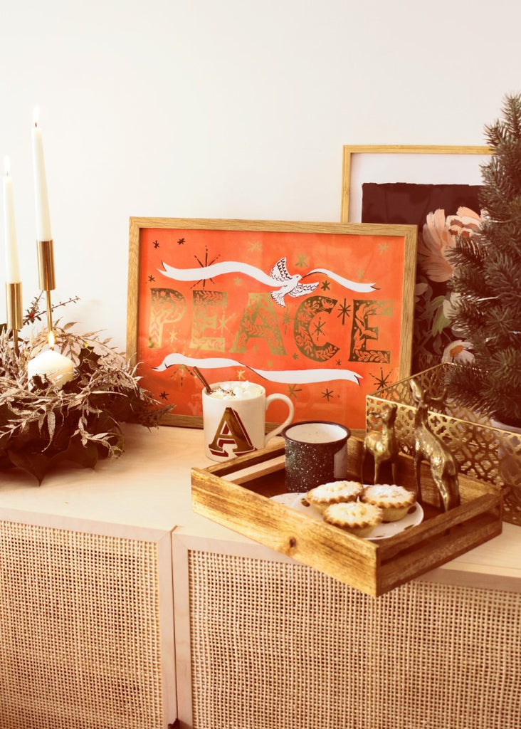 Gold foiled christmas print propped on a cabinet decorated with candles, and a tray of christmas treats