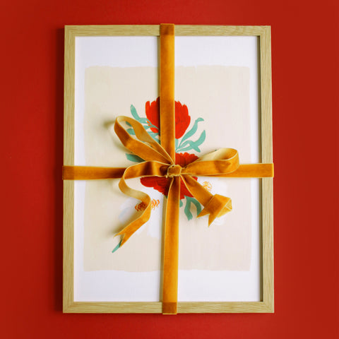 a framed print, tied with velvet ribbon on a red background