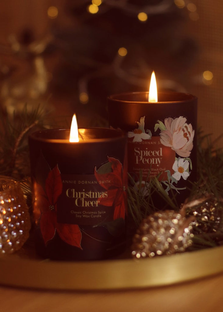 Two candles in black jars decorated with illustrated floral labels on a gold tray surrounded by christmas decorations