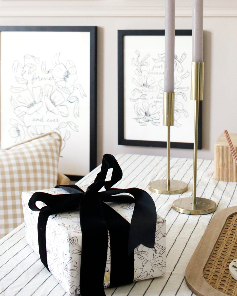 a gift wrapped in monochrome floral wrapping paper