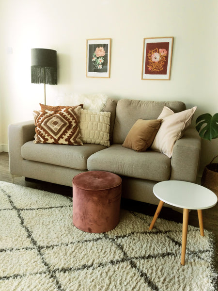 narrow living room style - greige sofa with a mini foot stool, standing lamp and wall art