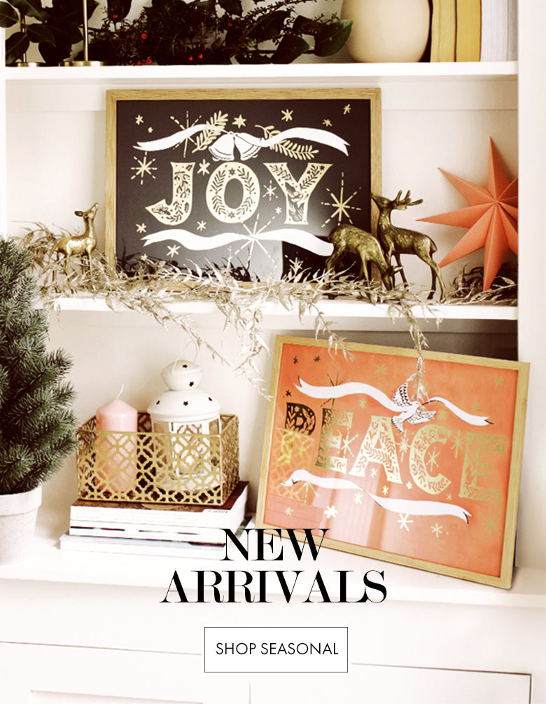 New Arrivals (Image: Christmas Prints propped on a bookshelf) - Click to Shop Seasonal