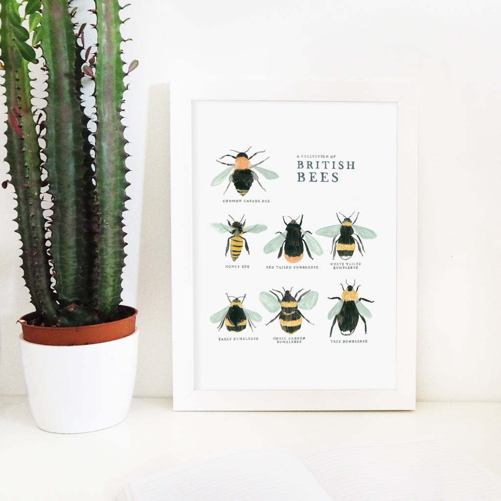 the british bee print in a white wooden frame with a potted plant on the left