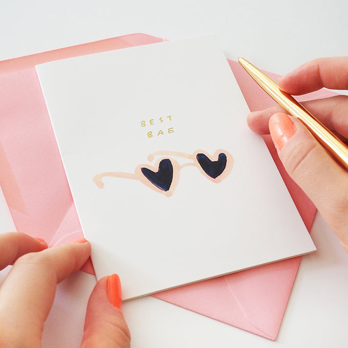 """holding a gold pen, about to write inside a white valentine's card that reads """"best bae"""" in gold, above a pair of illustrated heart shaped sunglasses."""