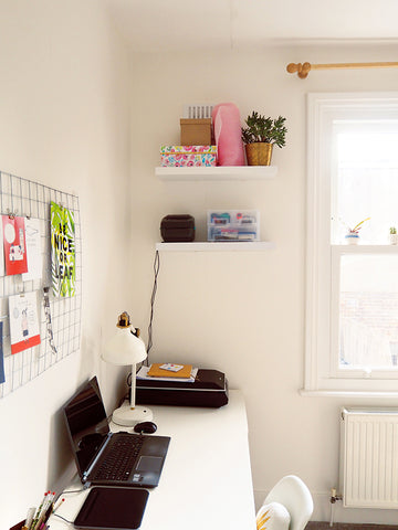 Annie's home office workspace - a long desk along the wall with open shelving for printing labels