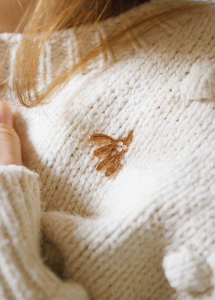 A rose gold enamel pin in the shape of a sprig of Mistletoe, pinned on a soft white jumper