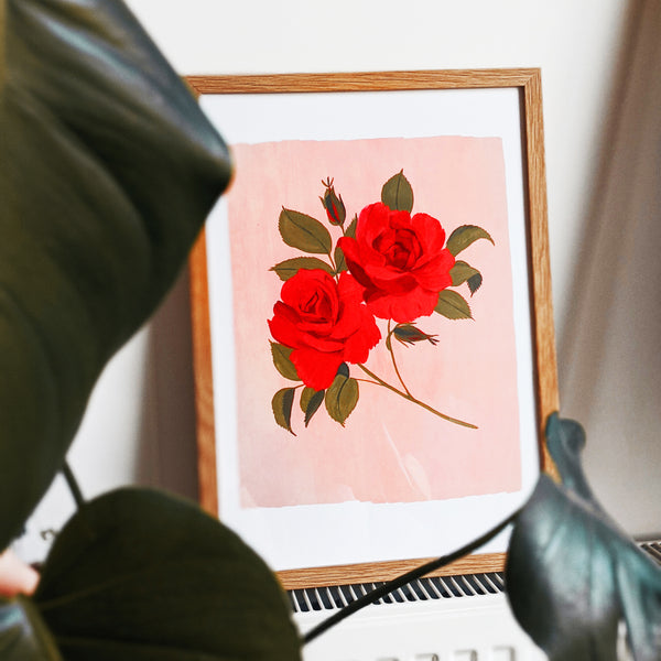 a framed print of painted roses propped on a radiator surrounded by houseplant leaves