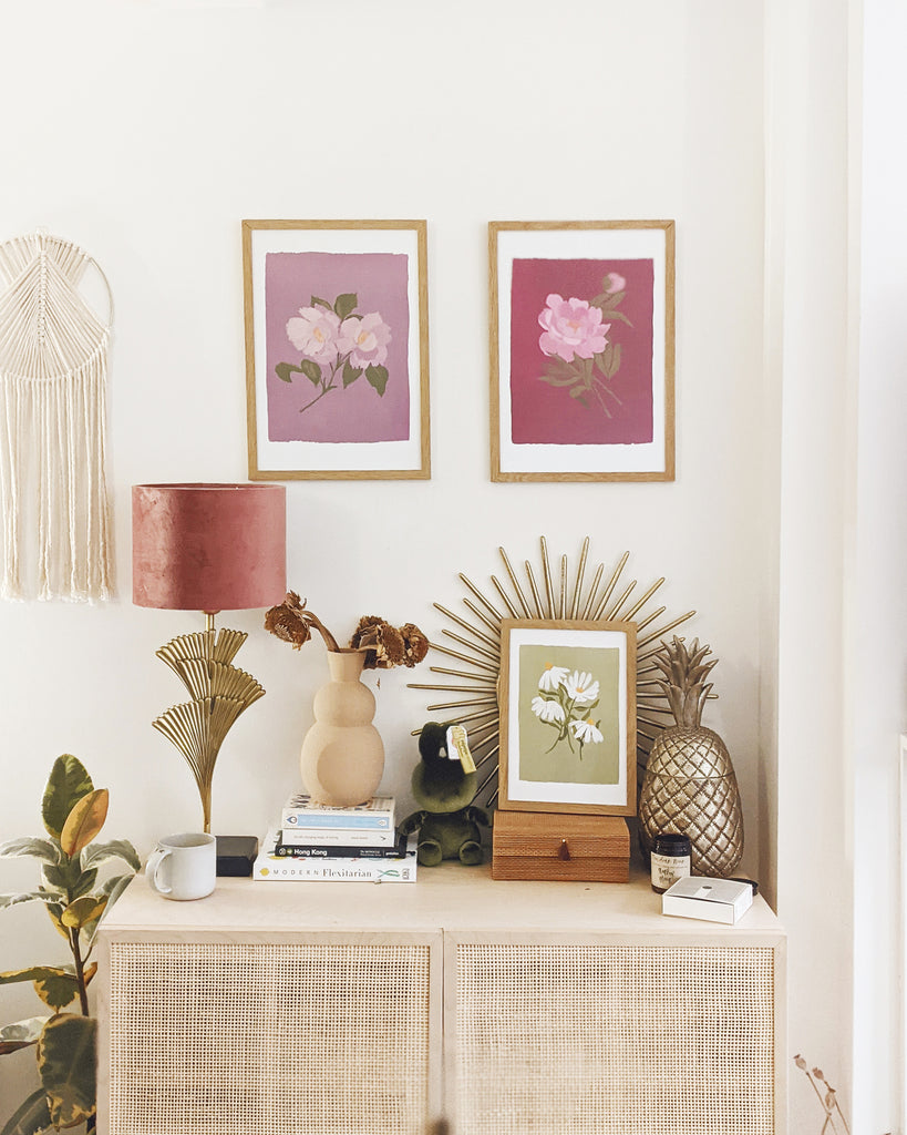 two floral prints - one deep pink and one pale lilac - framed, hanging above a rattan cabinet, decorated with al lamp, books, a vase of dried flowers and a framed green floral print