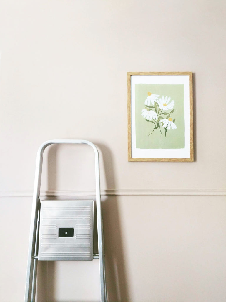 a green floral print in a pale wood frame, hanging on a pale lilac wall, next to a set of stepladders