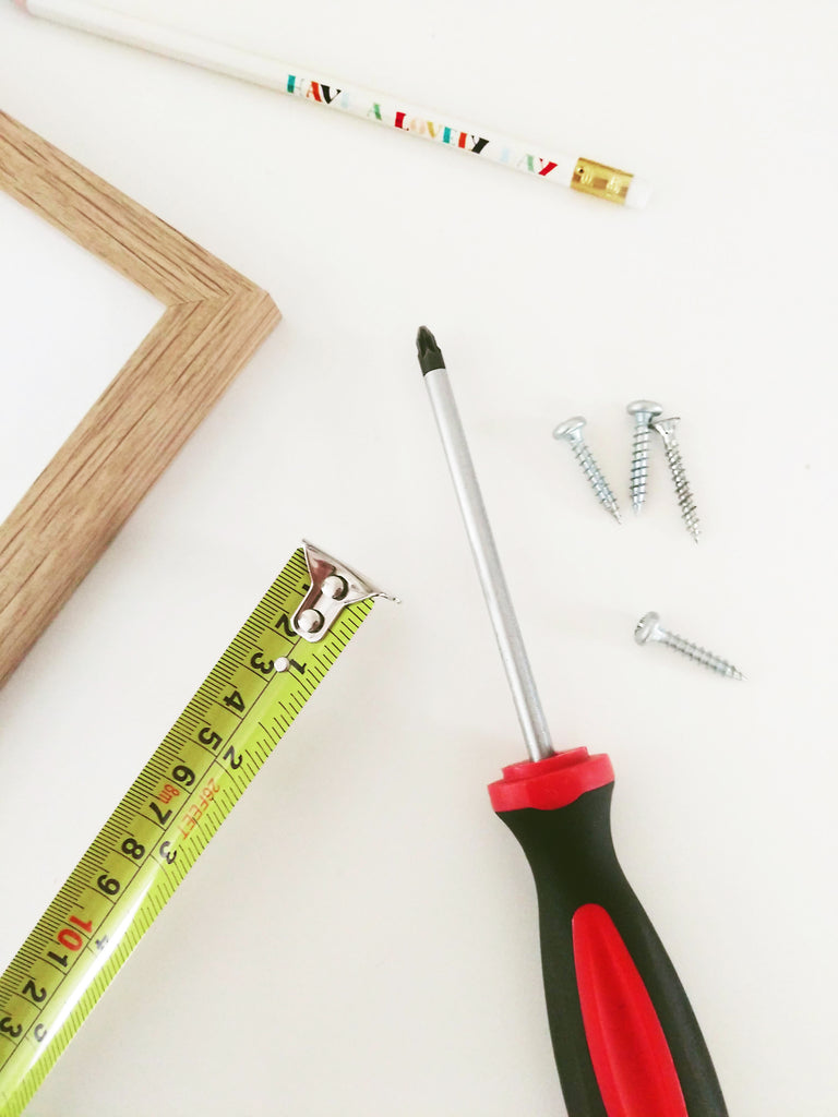 a frame, tape measure, screwdriver, pencil and screws laid out on a table