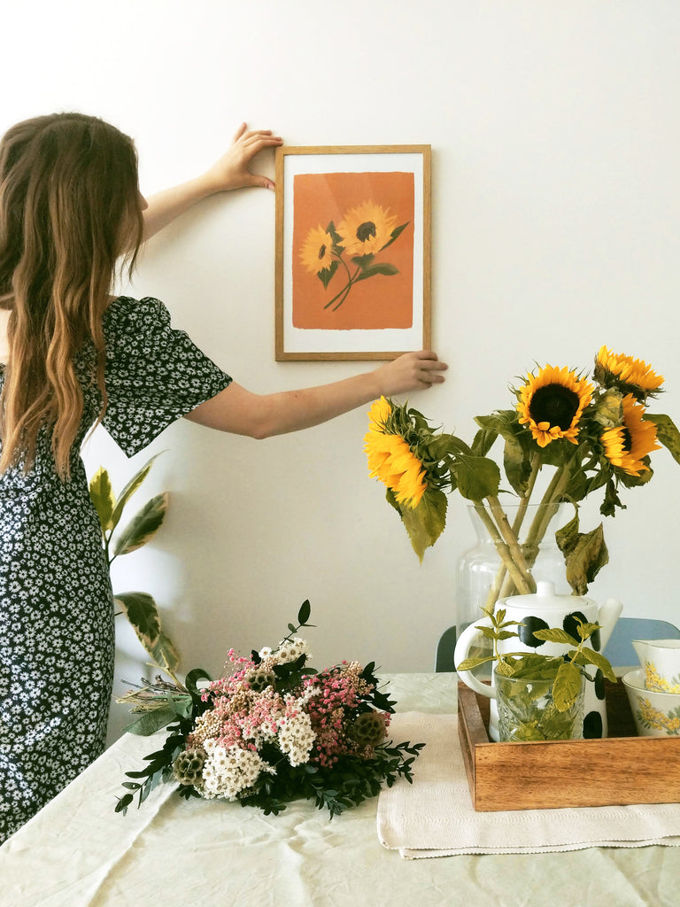 Annie, wearing a floral dress, hanging a sunflower print in a wooden frame, above a table with dried flowers and a vase of sunflowers.