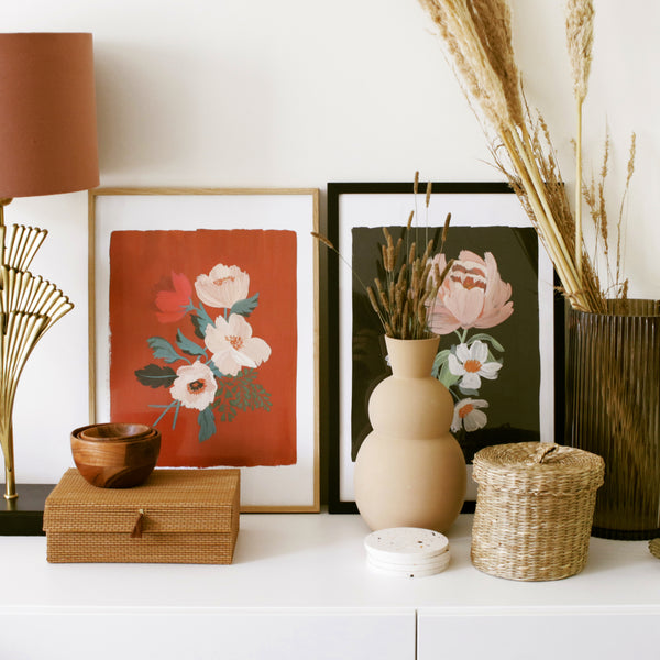 A side cabinet decorated with moody-hued floral prints and wicker and rattan storage boxes