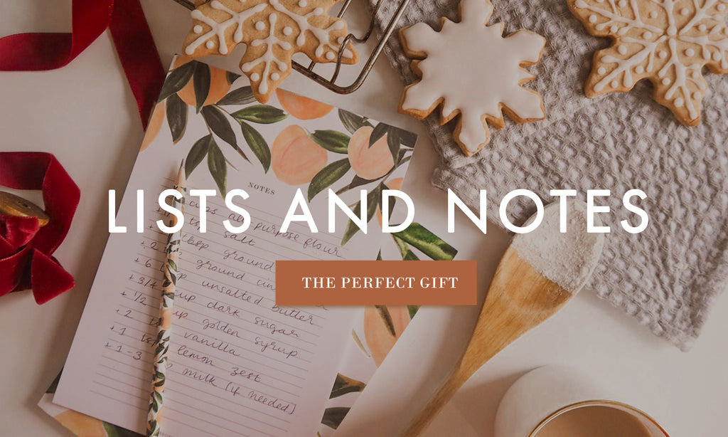 a peach patterened notebook with a recipe noted down on it lays on a table, surrounded by freshly iced christmas cookies and baking equipment. Overlaid, some text reads