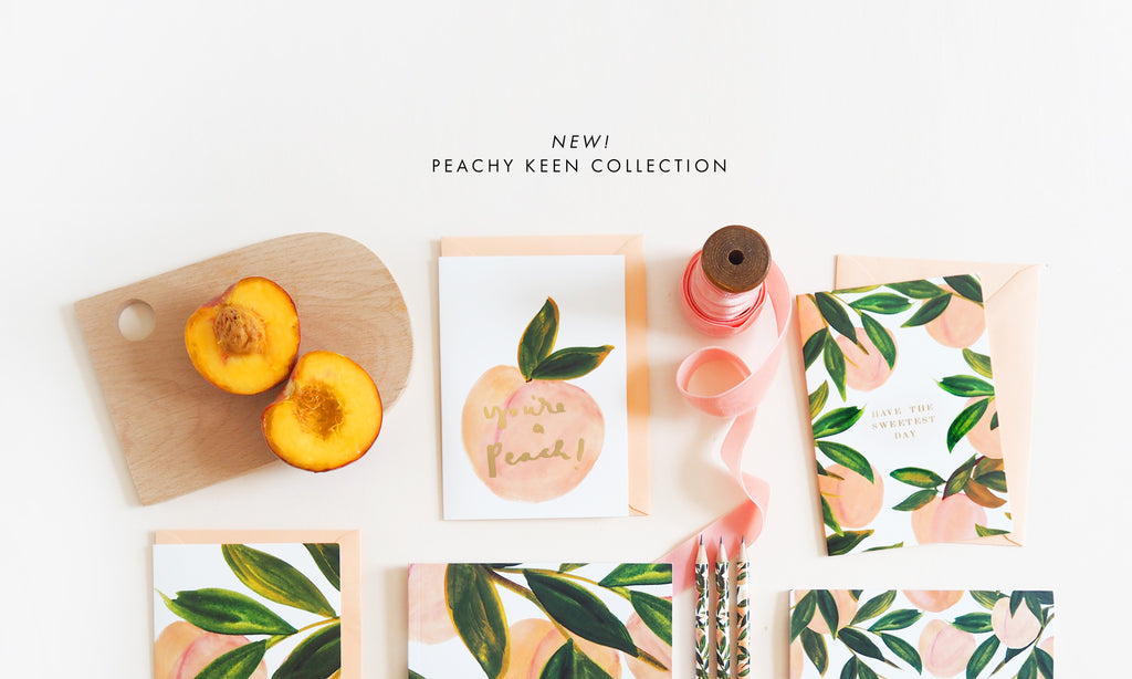 a group of cards and stationery covered in illustrated peaches, alongside peach ribbon and fresh peaches