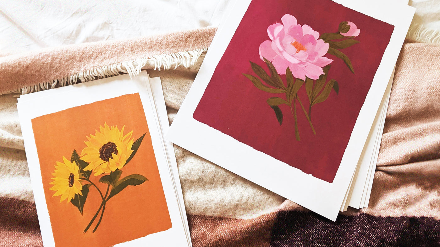 Shop the new Spring Florals collection! (Img: two painted floral prints with bright coloured backgrounds lay of a pink blanket ready to be hung)