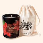a black christmas candle decorated with a floral label, alongside a lined bag, illustrated with a black flower